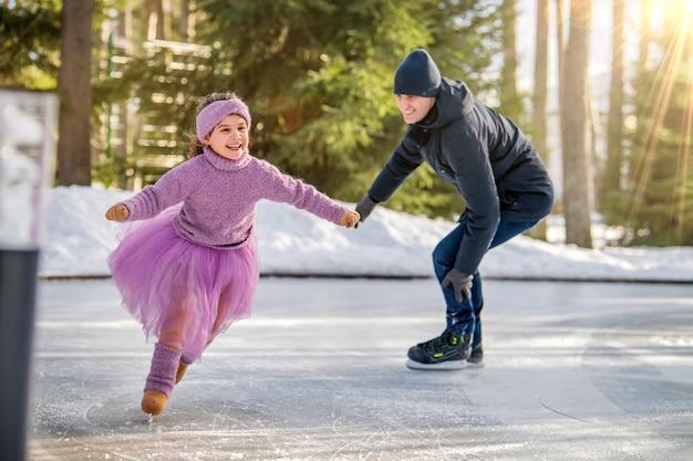 Une petite fille vêtue d'un pull rose et d'une jupe moelleuse par une journée d'hiver ensoleillée monte avec son père sur une patinoire ouverte dans le parc
