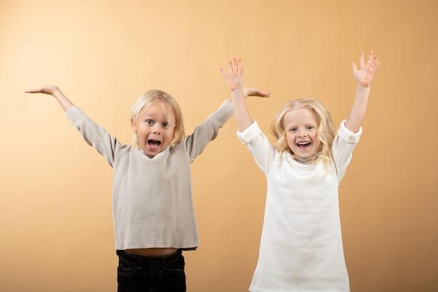 Une petite fille vêtue d'une robe blanche et d'un bonnet noir et d'un garçon en pull.