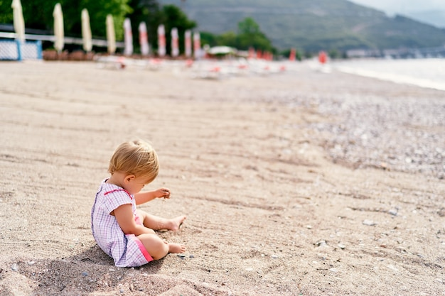 Petite fille vêtue d'une robe joue avec du sable sur la vue latérale de la plage
