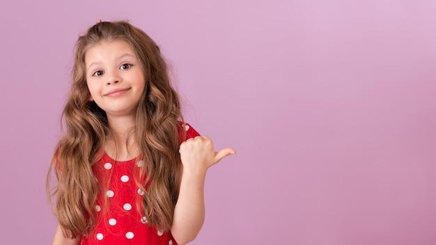Une petite fille vêtue d'une robe à pois rouge pointe son doigt sur le côté.