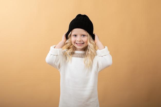 Une petite fille vêtue d'une robe tricotée blanche et d'un chapeau noir.
