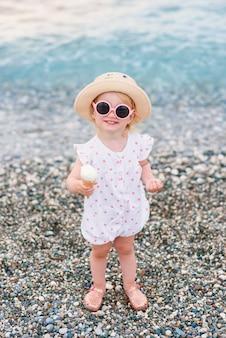 Une petite fille vêtue de vêtements d'été, d'un chapeau jaune et de lunettes de soleil roses se tient sur la plage, mange de la glace blanche et regarde la caméra.