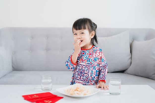 Petite fille vietnamienne en robe traditionnelle ao dai, fête le nouvel an à la maison. vacances du têt.