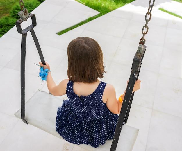 Petite fille vole sur la balançoire dans la cour de la maison