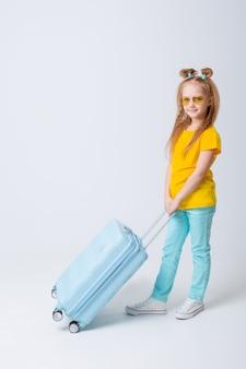 Petite fille voyageuse avec une valise sur blanc