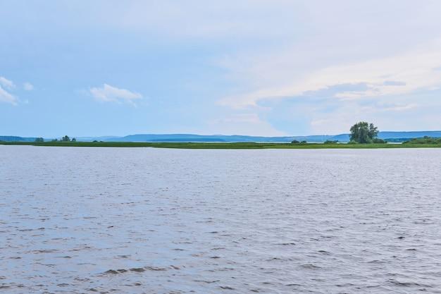 Petite île aux roseaux au milieu d'une large rivière