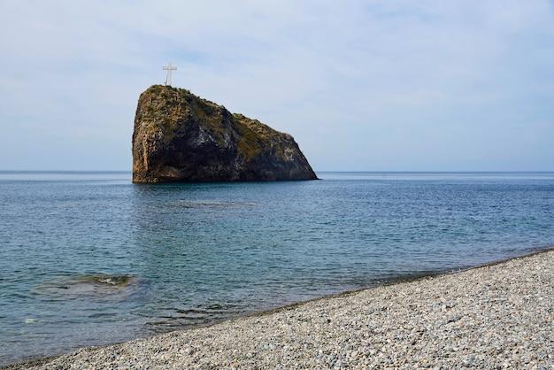 Une petite île avec une croix dans la mer près de la côte.
