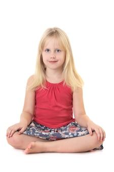 Petite jeune fille assise et souriante isolée