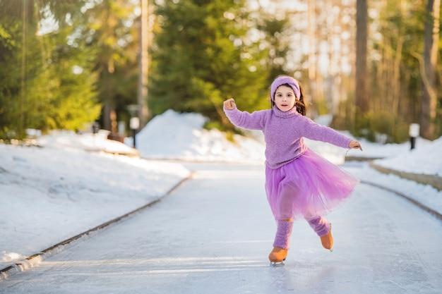 Petite jeune fille vêtue d'un pull rose et d'une jupe ample se promène par une journée d'hiver ensoleillée sur une patinoire extérieure dans le parc