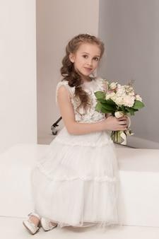 Petite jolie fille avec des fleurs vêtues de robes de mariée