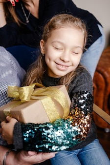 Petite jolie fille heureuse étreignant son cadeau de noël. enfant excité à l'idée de déballer son cadeau