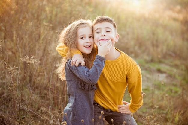 Petite jolie fille et jeune garçon s'embrassant le jour de l'automne