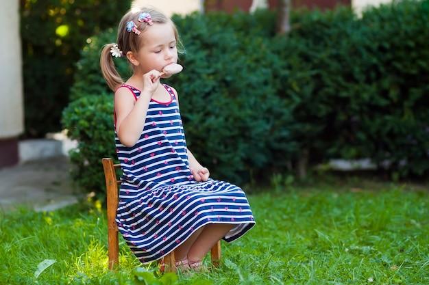 Petite jolie fille en journée d'été mangeant une glace