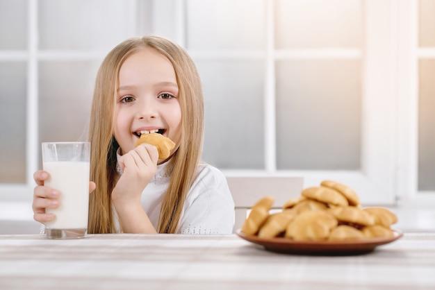 Petite jolie fille mangeant un biscuit sucré.