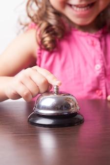 Petite jolie fille pousse sur la cloche, jeu de société à l'heure