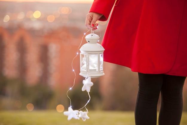 Petite lanterne avec illumination magique tenue par une femme en manteau rouge