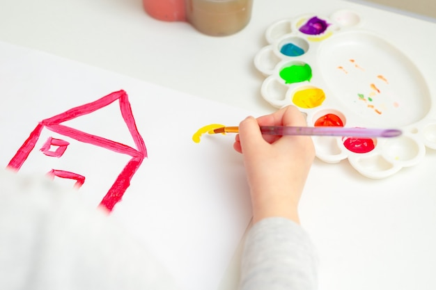 Petite main d'enfant dessinant maison et soleil à l'aquarelle. concept d'éducation et d'école.