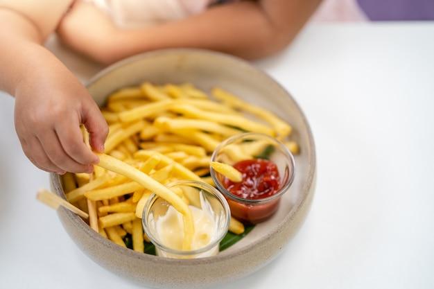 Petite main tenant des frites tremper dans une sauce mayonnaise