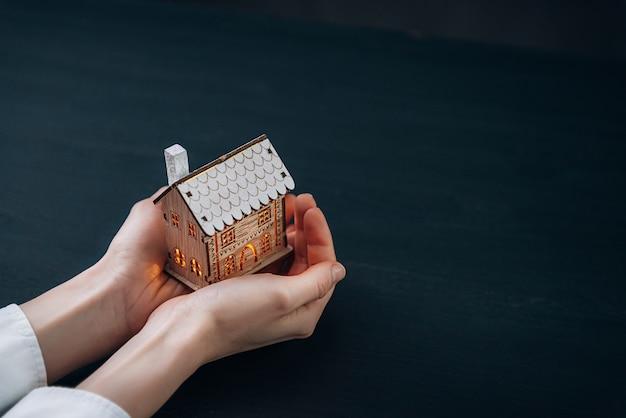 Petite maison aux fenêtres lumineuses entre les mains des femmes
