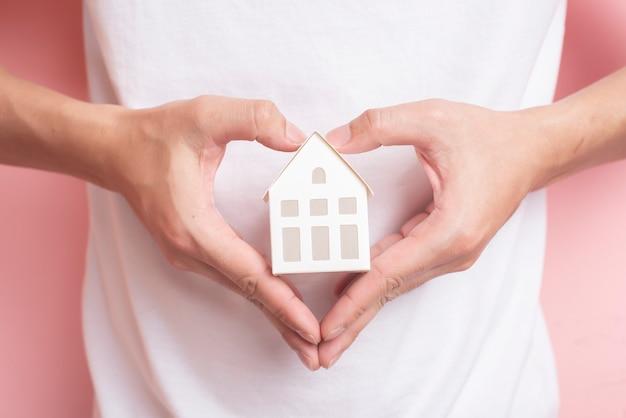 Petite maison blanche sur la main de l'homme