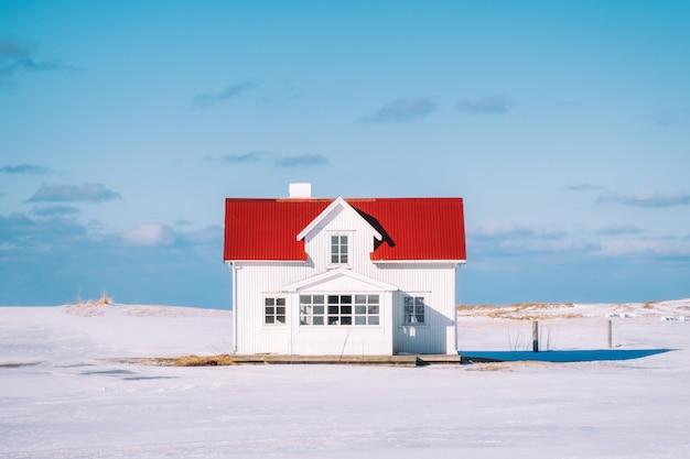 Petite maison blanche avec toit rouge et ciel bleu enneigé