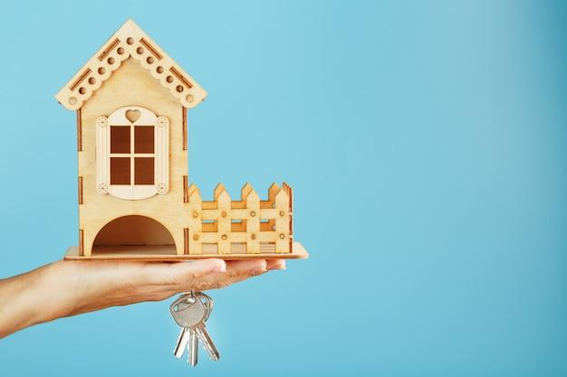 Une petite maison en bois avec clés en main sur fond bleu