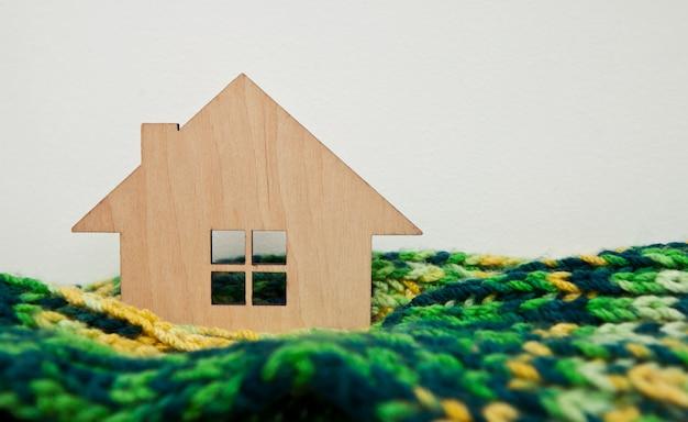 La petite maison en bois enveloppée dans le foulard posé sur le radiateur de la maison