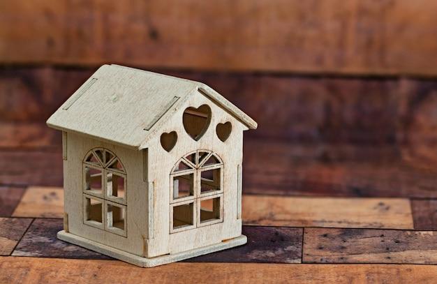 Petite maison en bois sur fond en bois.