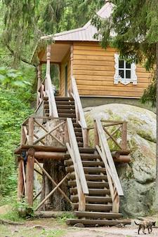 Petite maison en bois sur une grosse pierre dans la forêt