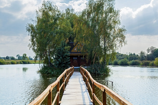 Petite maison sur l'île paysage avec pont à la maison sur le lac vieux bois