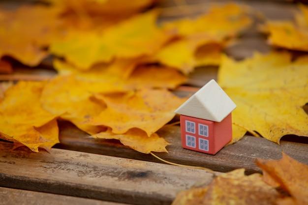 Petite maison de jouets à côté des feuilles d'automne sur une table