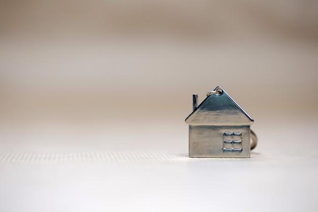 Petite maison miniature sur fond flou, nouvelle maison, immobilier, prêt hypothécaire, concept architectural avec copie espace espace texte fot