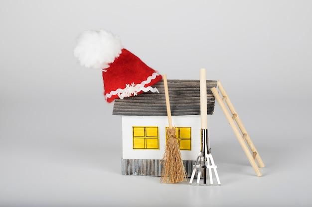 Petite maison en papier fait main et chapeau de père noël dessus. outils de jardinage en arrière-plan