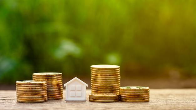 Petite maison et une pile de pièces d'or dans le jardin.
