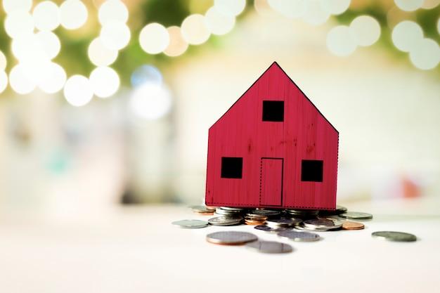 Petite maison rouge debout sur un tas de pièces de monnaie. le concept d'achat d'habitation