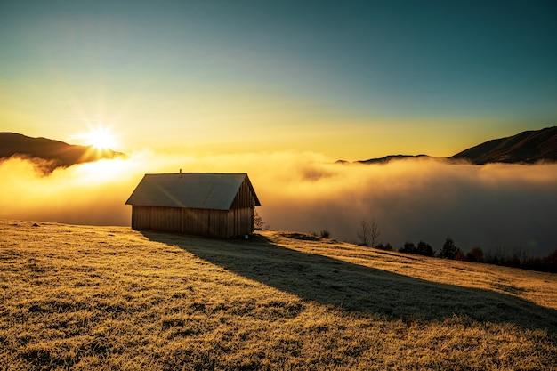 Une petite maison solitaire se dresse sur une prairie gelée sur fond de beau ciel bleu, de soleil éclatant et de brouillard blanc