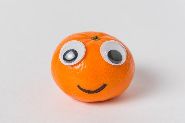Petite mandarine avec de grands yeux et un sourire. caractère mandarin sur blanc