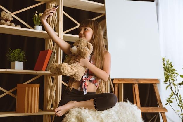 Petite mannequin assise dans sa chambre avec un smartphone et faisant des selfies ou utilisant un chat vidéo avec ses amis.