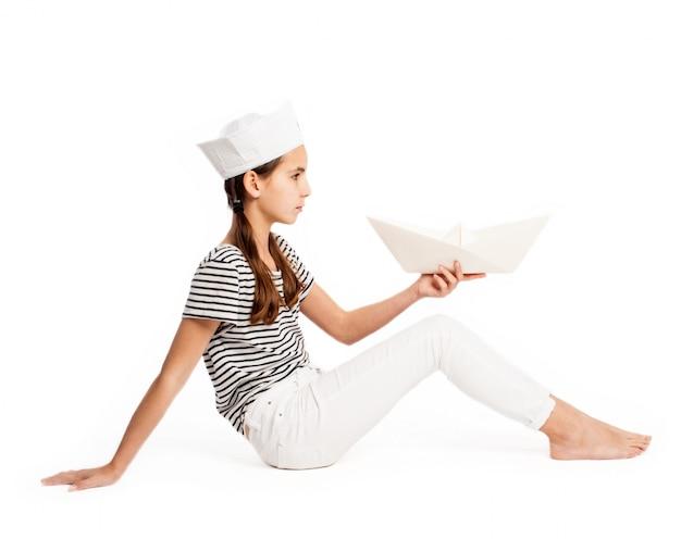 Petite marine tenant un bateau en papier sur un fond blanc