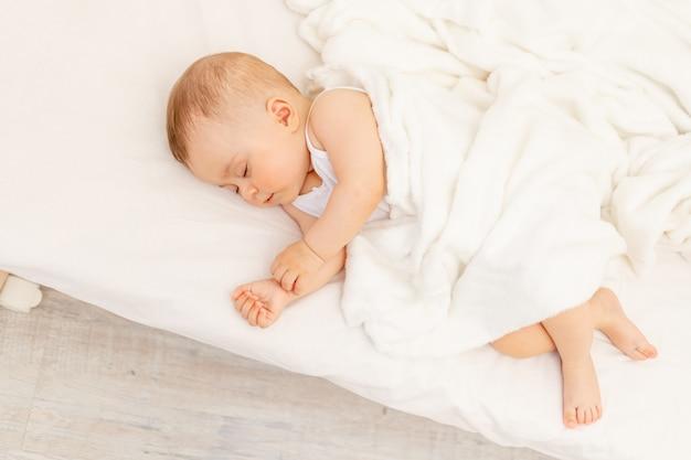 Petite petite fille de 6 mois dormant dans un lit blanc, sommeil de bébé sain