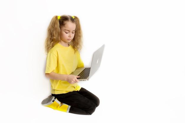 Petite petite fille européenne concentrée portant un t-shirt jaune assis devant un ordinateur vérifiant des tâches dans une salle de classe en ligne, concept d'apprentissage à distance en ligne.
