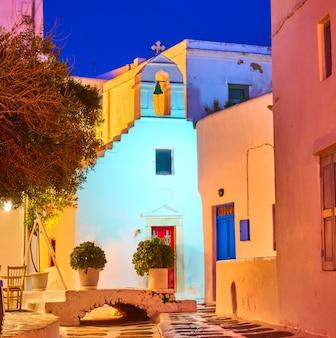 Petite place avec église blanche dans la ville de mykonos la nuit, grèce.