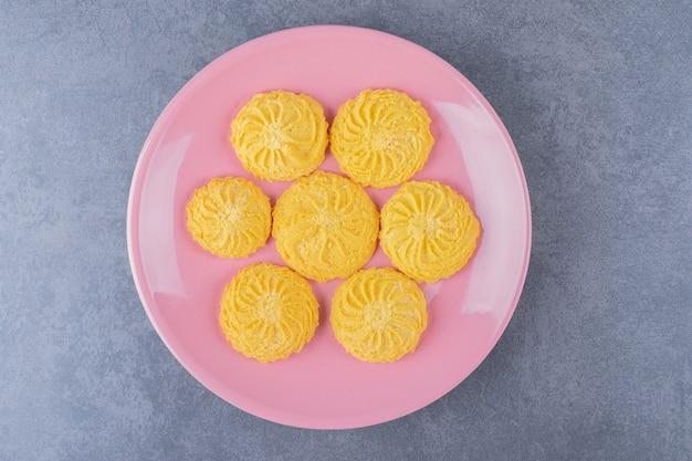 Une petite portion de biscuit sur une assiette sur une table en marbre.