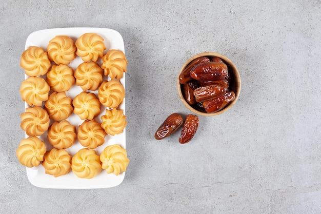 Une petite portion de dattes avec une assiette pleine de biscuits sur une surface en marbre