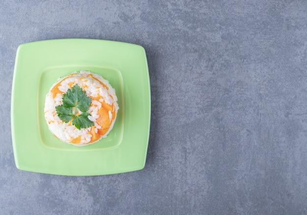 Une petite portion de riz aux carottes, sur la surface du marbre.