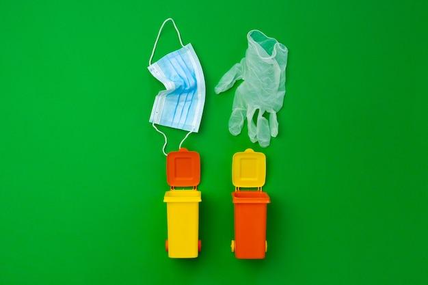 Petite poubelle colorée a utilisé des masques infectieux, gros plan