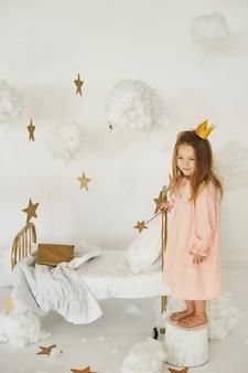 Petite princesse avec une baguette magique sur un lit dans un nuage sur fond blanc