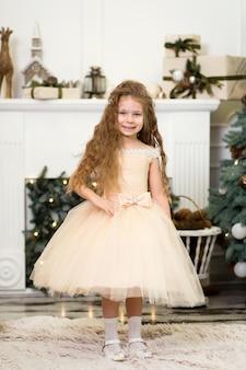 Petite princesse mignonne dans une robe chic rit et pose près de l'arbre de noël