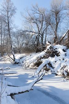 Une petite rivière dont l'eau est gelée en hiver, une rivière gelée pendant les gelées hivernales, la neige et le gel dans la nature en hiver près d'une rivière ou d'un lac