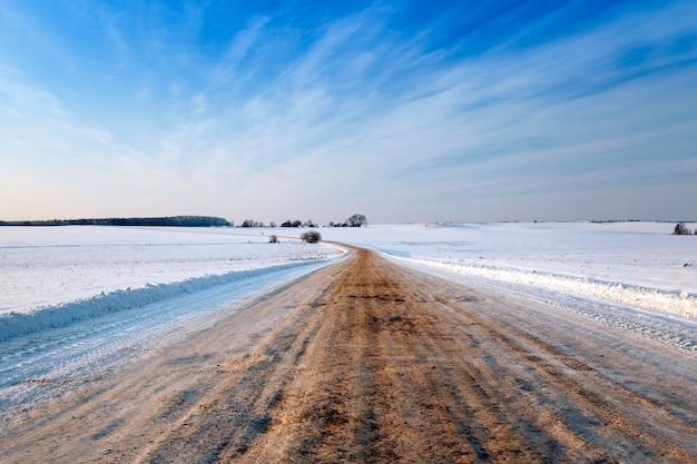 Une petite route de campagne passe dans un champ en hiver. couvert de neige